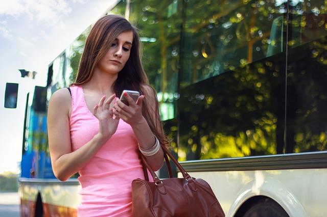 Fată utilizând Facebook de pe telefonul mobil